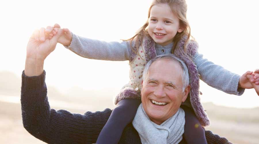 Anziano sorridente con bambina sulle spalle